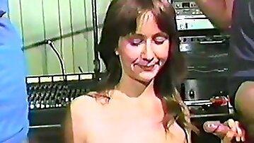 Shy slim brunette enjoys sucking two dicks in a vintage clip
