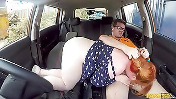 A fat redhead chick rides a stiff dick during a driving lesson